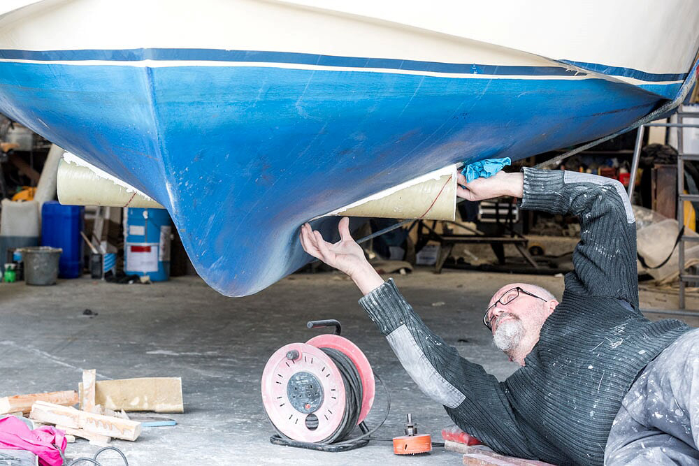 Man fixing the bottom of a boat out of water